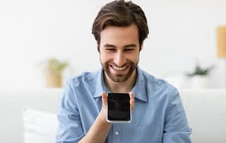 Cheerful Man Using Smartphone With Voice Search Application Sitting Indoor